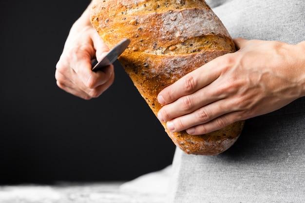 Pagnotta del pane di taglio del coltello del primo piano