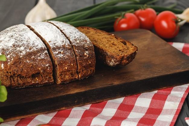 Pagnotta di pane affettata sul bordo di legno