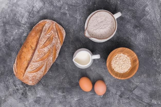 Pagnotta di pane al forno con ingredienti su sfondo concreto
