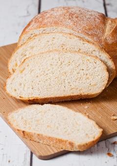 Pagnotta di pane appena sfornata con pezzi su tavola di legno bianco a bordo bianco