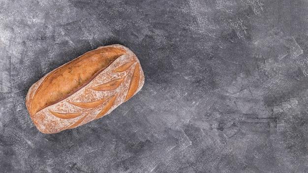 Pagnotta di pane appena sfornata su priorità bassa strutturata nera