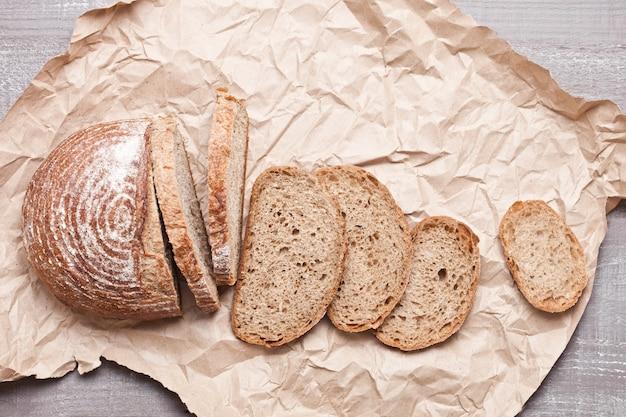 Pagnotta di pane appena sfornato con pezzi su tavola di legno bianco