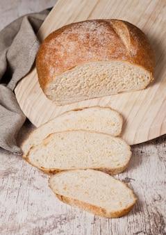 Pagnotta di pane appena sfornato con pezzi su tavola di legno di legno boardon con asciugamano da cucina
