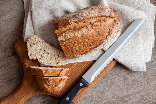 Pagnotta di pane integrale con le fette sul bordo di legno sul tavolo da cucina