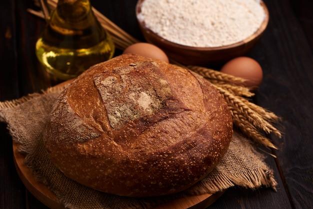 Pagnotta di pane su un fondo di legno, primo piano dell'alimento. sullo sfondo di farina e olio vegetale con uova.
