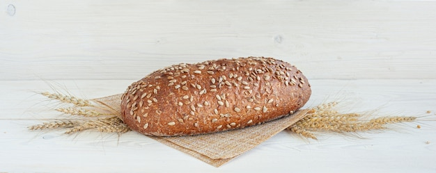 Pagnotta fresca di pane integrale con semi di girasole su un fondo di legno bianco. composizione con spighe di grano. banner.