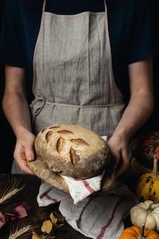 Pagnotta organica del pane di zucca di lievito naturale, mani femminili sulla tavola di legno scura