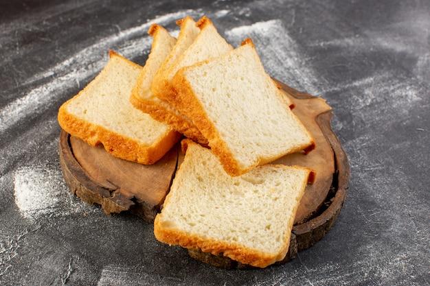 Pagnotte di pane bianco vista frontale affettate sullo scrittorio di legno