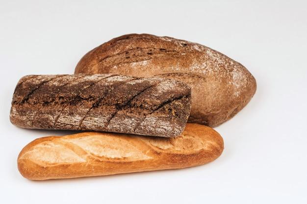 Pagnotte di segale e pane integrale su una priorità bassa bianca.