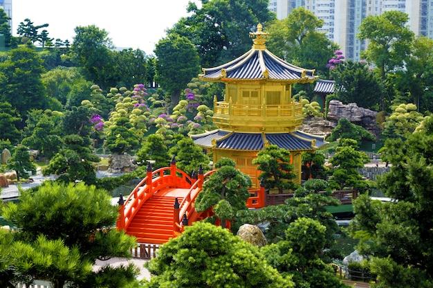 Pagoda dorata e ponticello rosso nei giardini di nan lian, città di kowloon, hong kong