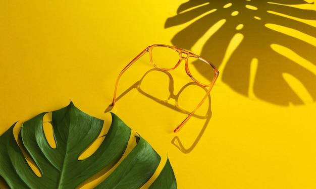 Paia degli occhiali da sole moderni alla moda delle donne accesi con luce intensa su fondo giallo luminoso astratto con l'ombra della foglia di monstera