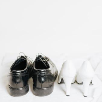 Paia dei tacchi alti di nozze e delle scarpe nere su fondo bianco