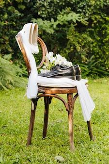 Paia dei tacchi alti e delle scarpe di nozze con il mazzo del fiore e della sciarpa su erba verde nel parco