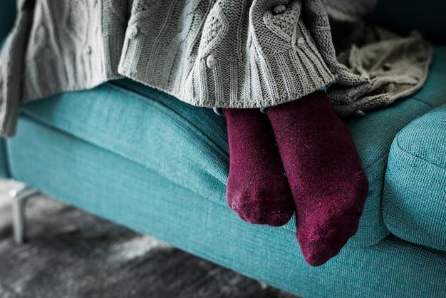 Paia del primo piano delle gambe sul sofà