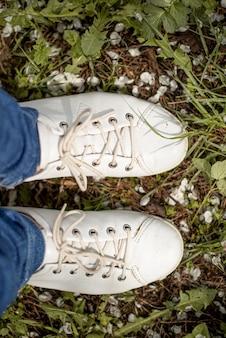 Paia delle scarpe bianche su erba verde