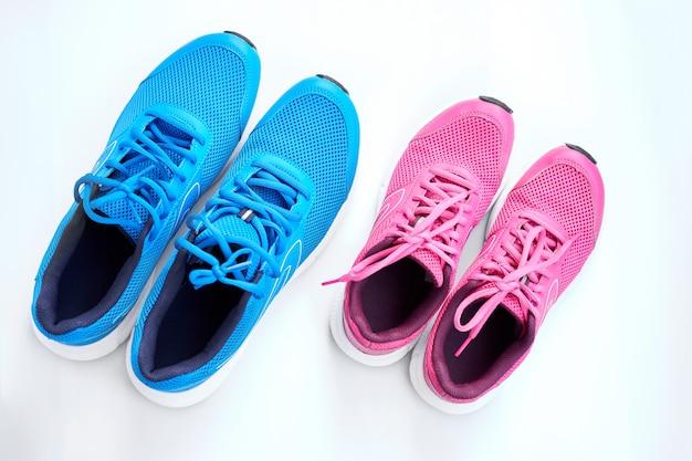 Paia delle scarpe da tennis blu degli uomini e paio delle scarpe da tennis rosa delle donne su fondo bianco.