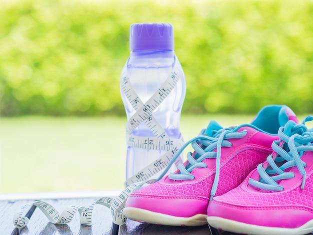 Paia delle scarpe e della bottiglia di acqua rosa di sport con il fondo verde del bokeh