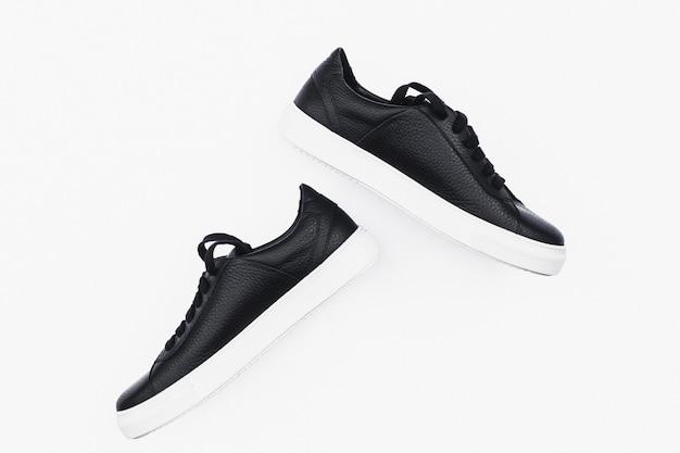 Paia di nuove scarpe da tennis in pelle nera isolate
