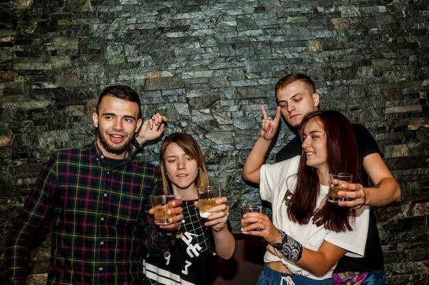 Paio di cocktail in possesso di coppia in piedi contro il muro