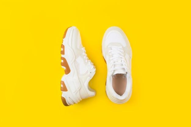 Paio di eleganti scarpe da ginnastica bianche su sfondo giallo.