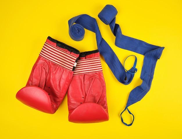 Paio di guanti da boxe in pelle rossa e fasciatura in tessuto blu