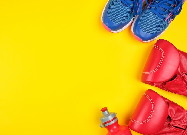 Paio di guanti da boxe rossi e scarpe da ginnastica blu