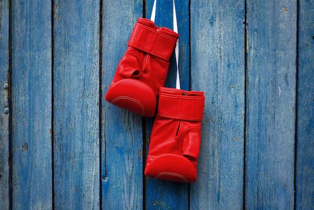 Paio di guanti rossi per kickboxing appesi a una corda bianca