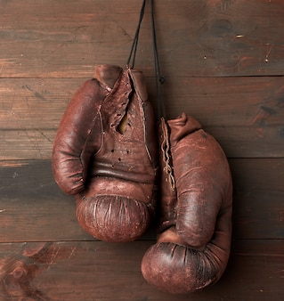 Paio di guantoni da boxe in pelle marrone appesi su una parete di legno