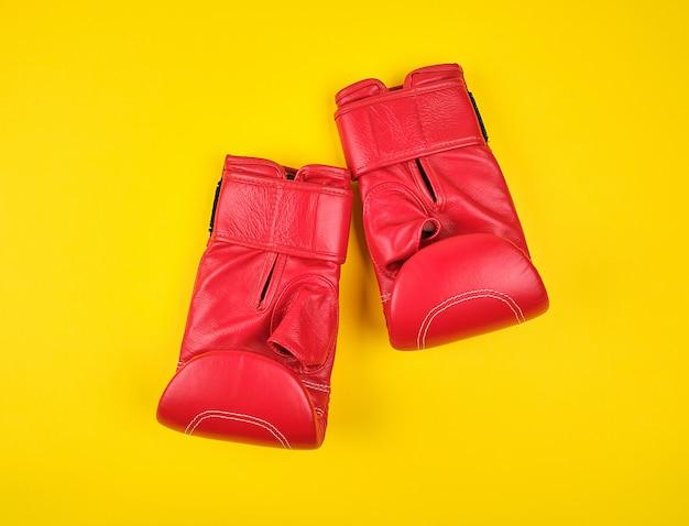 Paio di guantoni da boxe in pelle rossa su uno sfondo giallo