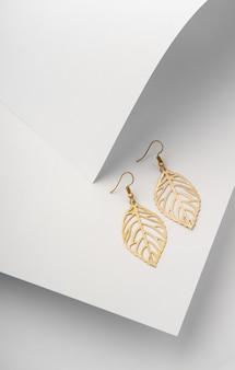 Paio di orecchini a forma di foglie su carta bianca piegata