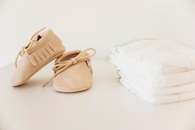 Paio di scarpe da bambino e impilati di pannolini su fondo beige