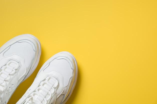 Paio di scarpe da ginnastica bianche femminili su giallo. flat lay, top view minimal.