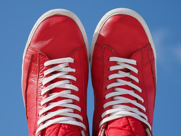 Paio di scarpe da ginnastica rosse con lacci bianchi cielo blu.