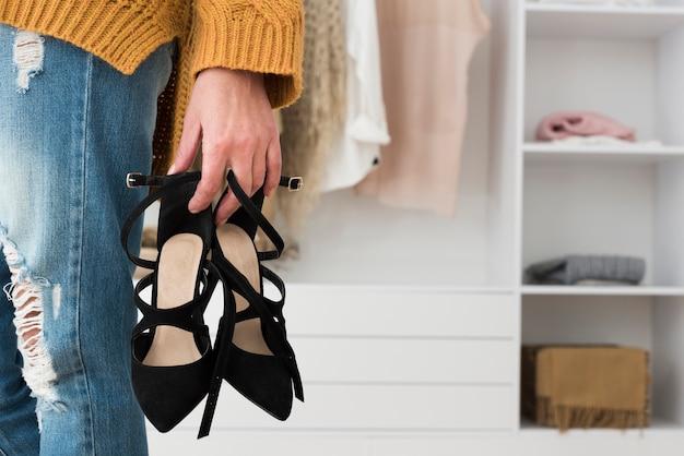 Paio di scarpe del primo piano tenuto in mano dalla donna più anziana