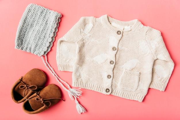 Paio di scarpe di lana; berretto e vestiti del bambino su sfondo di pesca