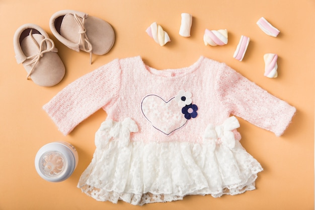 Paio di scarpe; marshmallow; bottiglia di latte e vestito rosa baby su uno sfondo arancione