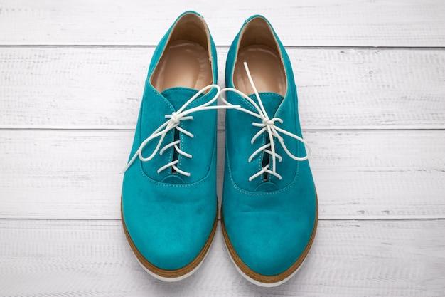 Paio di scarpe scamosciate color acqua. stivali verdi con pizzi bianchi su un fondo di legno leggero, vista dall'alto.