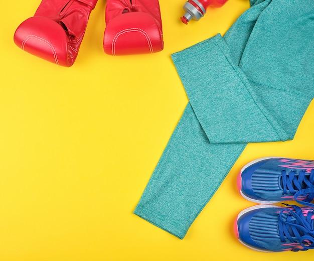 Paio di sneakers blu, guantoni da boxe in pelle rossa