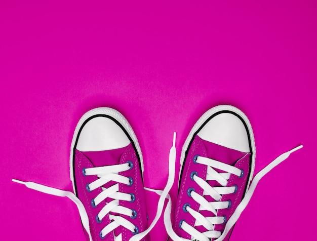 Paio di sneakers in tessuto rosa con lacci bianchi