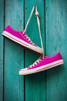 Paio di sneakers rosa brillante appeso a un cavo