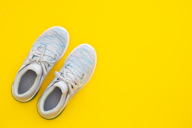 Paio di sneakers sportive alla moda su sfondo giallo.