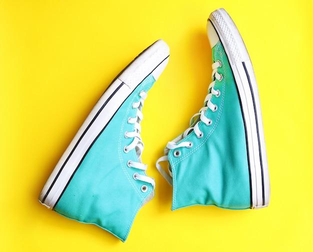Paio di vecchie scarpe da tennis blu isolato su giallo