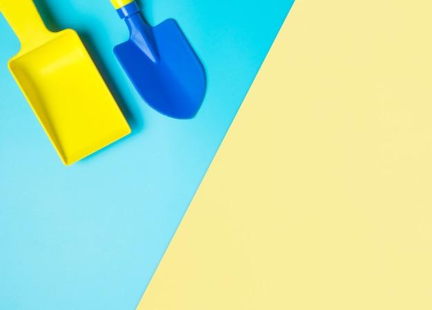 Pala di plastica variopinta di estate della sabbia su fondo blu e giallo