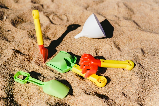 Pale e rastrelli da giocare sulla spiaggia in estate sulla sabbia, abbandonati.