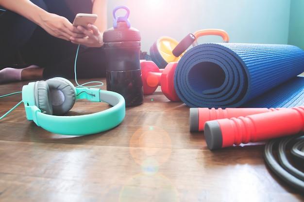 Palestra e attrezzature per il fitness a casa con la donna tramite smartphone