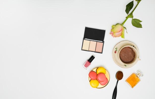 Paletta compatta per cipria; rosa; bottiglia di smalto per unghie; pennello da trucco ovale; bottiglia di profumo e caffè su sfondo bianco
