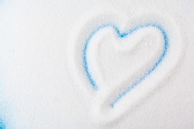 Paletta con sabbia bianca e zolletta di zucchero vicino sfondo