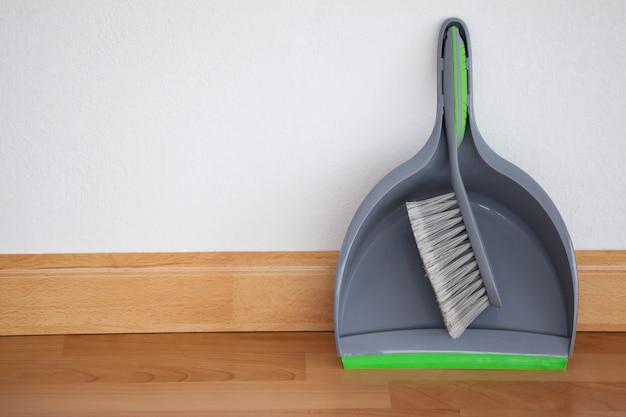 Paletta per la spazzatura e spazzola ampia appoggiata al muro bianco