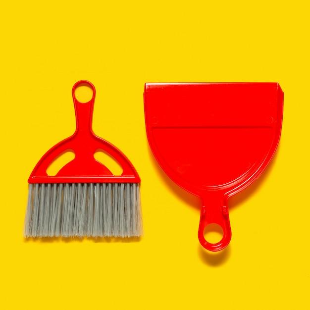 Paletta per la spazzatura rossa e spazzola che si trovano sul giallo