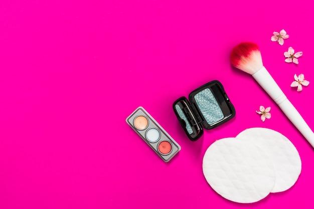 Palette di ombretti; pennello da trucco; tamponi di cotone e fiori su sfondo rosa